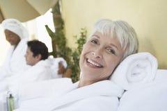 Frau, die am Badekurort im Bademantel sich entspannt Stockfoto