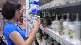 Frau, die Badezimmerzubehör im Speicher wählt stock footage
