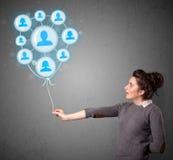 Frau, die Ballon des Sozialen Netzes hält Stockfotos