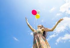 Frau, die Ballone freigibt Stockfotografie
