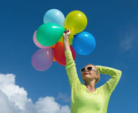 Frau, die Ballone gegen Wolke hält Lizenzfreies Stockfoto