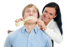 Frau, die Band auf Mund des Mannes anbringt. Lizenzfreie Stockfotos