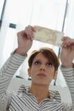 Frau, die Banknotewasserzeichen überprüft Lizenzfreie Stockfotografie