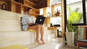 Frau, die barfüßigfunktion auf ihrem Laptop sitzt stock video footage