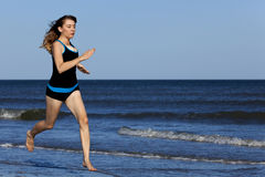 Frau, die barfuß auf dem Strand läuft stockfoto