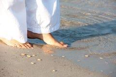 Frau, die barfuß auf den Strand geht Lizenzfreies Stockfoto