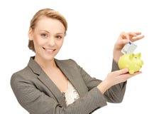 Frau, die Bargeld in kleines Sparschwein steckt Stockbild
