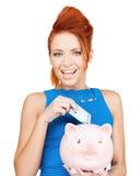 Frau, die Bargeld in Sparschwein steckt Stockbilder