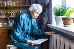 Frau, die Bargeld vor Heizungsheizkörper hält Zahlung für die Heizung im Winter Selektiver Fokus stockfotografie