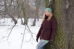 Frau, die am Baum in der Winterlandschaft sich lehnt Stockbild