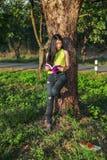 Frau, die am Baum stading und ein Buch im Park gelesen worden sein würden lizenzfreie stockfotografie