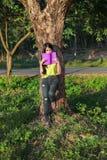 Frau, die am Baum stading und ein Buch im Park gelesen worden sein würden stockfotografie