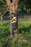 Frau, die am Baum stading und ein Buch im Park gelesen worden sein würden lizenzfreie stockfotos