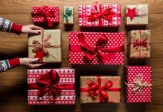 Frau, die beautifuly eingewickelte WeinleseWeihnachtsgeschenke auf hölzernem Hintergrund organisiert stockfotos