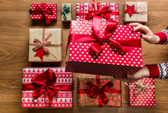 Frau, die beautifuly eingewickelte WeinleseWeihnachtsgeschenke auf hölzernem Hintergrund organisiert lizenzfreies stockbild