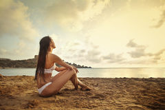 Frau, die bei dem Sonnenuntergang anstarrt stockfotos