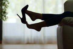 Frau, die bei den Füßen Schuhe entfernend liegt Stockfotografie