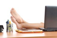 Frau, die bei der Arbeit mit den Füßen über dem Bürotisch stillsteht lizenzfreies stockbild