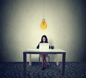 Frau, die bei Tisch das Arbeiten auf Laptop mit heller Glühlampe über Kopf sitzt lizenzfreies stockbild