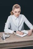 Frau, die bei Tisch sitzt und Anmerkungen macht Lizenzfreies Stockbild