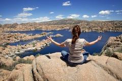 Frau, die bei Watson Lake meditiert Stockfoto