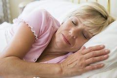 Frau, die beim Bettschlafen liegt Stockbild
