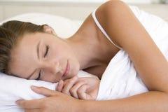 Frau, die beim Bettschlafen liegt Stockbilder