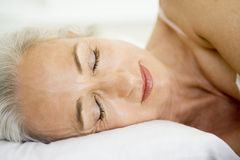 Frau, die beim Bettschlafen liegt Lizenzfreie Stockfotografie