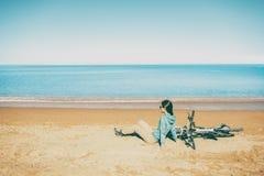 Frau, die beim Fahrrad auf Strand liegt Stockfoto