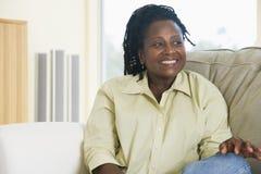 Frau, die beim Wohnzimmerlächeln sitzt Stockfotos