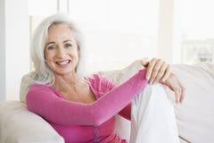 Frau, die beim Wohnzimmerlächeln sitzt Stockbild