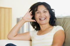 Frau, die beim Wohnzimmerlachen sitzt Stockfotografie