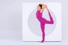 Frau, die Beine im modernen, weißen Innenraum ausdehnt Stockfotografie