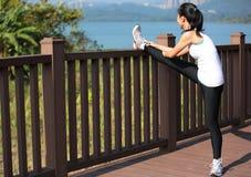 Frau, die Beine im Stadtpark ausdehnt Lizenzfreie Stockbilder