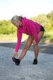 Frau, die Beinmuskeln ausdehnt Stockfotos