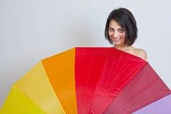 Frau, die über buntem Regenschirm sich versteckt Stockbild