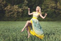 Frau, die über dem Feld an einem sonnigen Tag frei schwebt Stockfoto