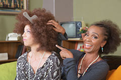 Frau, die über dem Haar des Freunds sich lustig macht Lizenzfreies Stockbild