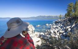 Frau, die über schöner Küstenlinie von Lake Tahoe schaut Stockfoto