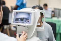 Frau, die Berechnungsmessersehtestmaschine in der Augenheilkunde betrachtet stockbild