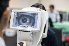 Frau, die Berechnungsmessersehtestmaschine in der Augenheilkunde betrachtet lizenzfreie stockfotos