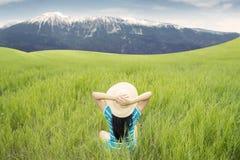 Frau, die Bergblick auf Wiese genießt Stockfotografie