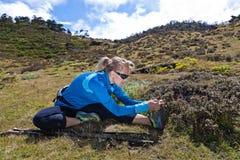 Frau, die in Berge trainiert und ausdehnt Lizenzfreie Stockfotos