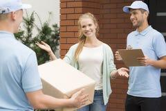 Frau, die Berufskuriere mit Paket und Ablieferungsbescheinigung begrüßt stockfotos
