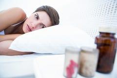 Frau, die beschließt, Pillen einzunehmen oder nicht Lizenzfreie Stockbilder