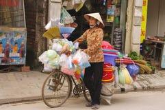 Frau, die Besen und Plastiknachrichten verkauft stockfotografie