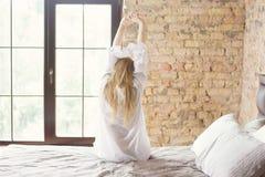 Frau, die in Bett nachdem dem Aufwachen ausdehnt Lizenzfreies Stockbild
