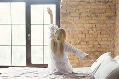 Frau, die in Bett nachdem dem Aufwachen ausdehnt Lizenzfreie Stockfotos