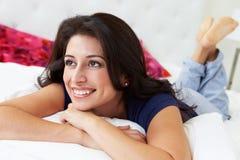 Frau, die in Bett-tragenden Pyjamas sich entspannt Stockbild