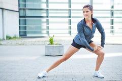 Frau, die bevor dem Laufen ausdehnt stockfotos